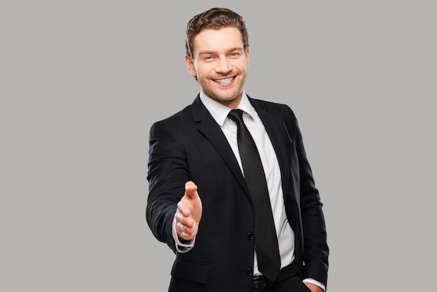 Gefeliciteerd! portret van een vrolijke jongeman in formalwear die zijn hand uitstrekt om te schudden terwijl hij tegen een grijze achtergrond staat