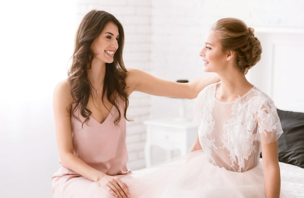 Gefeliciteerd. vrolijk lachend jong bruidsmeisje zittend in de witte kamer terwijl ze de bruid feliciteerde met haar trouwdag en geluk uitdrukte