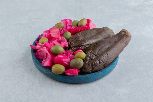Gefermenteerde aubergines en kool op blauw bord.