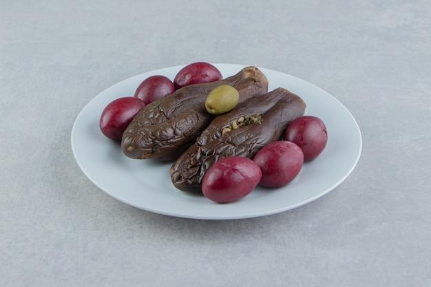 Gefermenteerde aubergines en pruimen op witte plaat.
