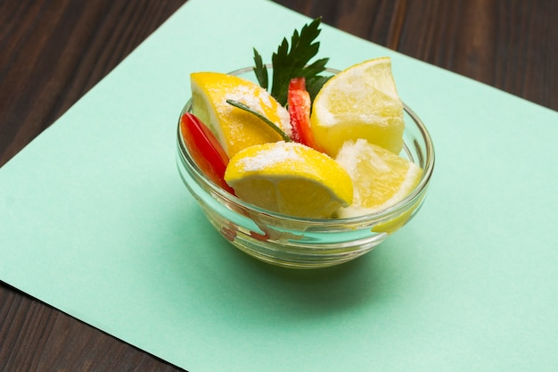 Gefermenteerde citroenen met zout en chilipeper. probiotica gefermenteerd voedsel. ingelegde citroenen. turkoois oppervlak. detailopname