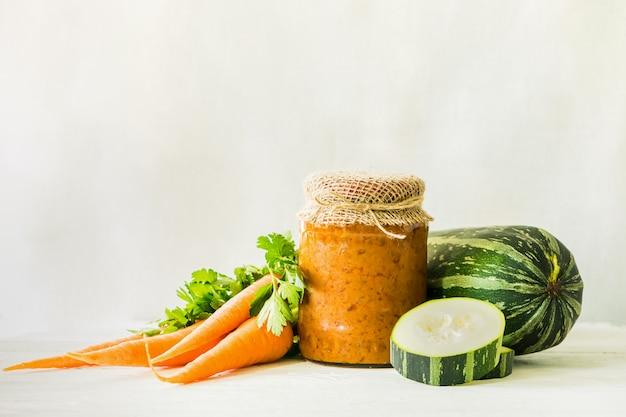 Gefermenteerde geconserveerde conserven diverse groenten courgette wortelen in glazen potten op tafel ingeblikt voedsel.