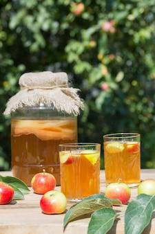 Gefermenteerde kombucha-drank in een glazen pot en twee glazen met een drankje met appels op de voorgrond, op een zonnige zomerdag in de tuin op een houten tafel.