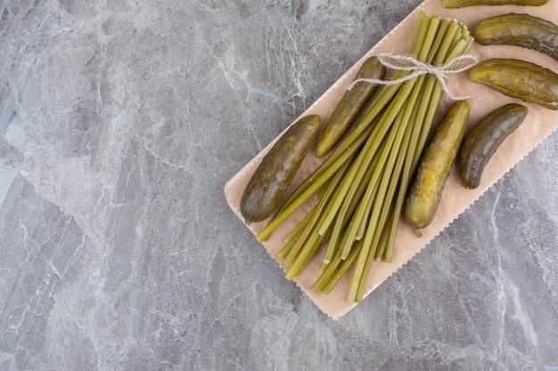 Gefermenteerde komkommers en sperziebonen op een houten bord.