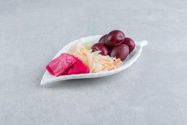 Gefermenteerde kool en fruit op bladvormige plaat.