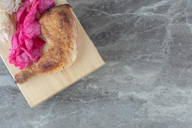 Gefermenteerde kool met gegrilde kip op een houten bord.