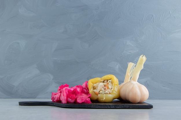 Gefermenteerde kool, peper en knoflook op zwart bord.