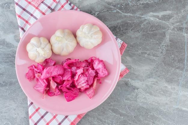 Gefermenteerde kool. zuurkool met ingemaakte knoflook op roze plaat.