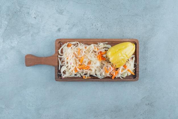 Gefermenteerde peper en zuurkool op een bord, op de blauwe tafel.