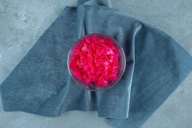 Gefermenteerde rode kool ligt in een kom op een stuk stof, op de blauwe tafel.