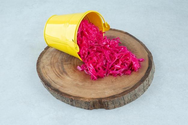 Gefermenteerde rode kool uit gele emmer op houten stuk.