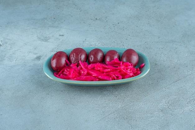 Gefermenteerde rode zuurkool met pruimen op een bord, op de blauwe tafel.