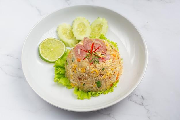 Gefermenteerde varkensvlees gebakken rijst geserveerd met verse komkommer