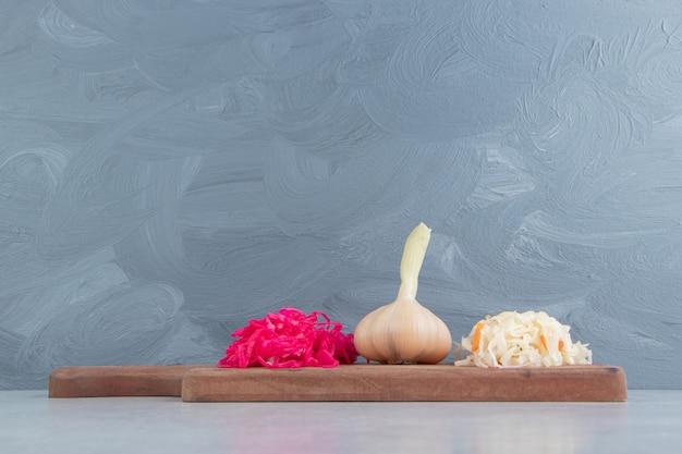 Gefermenteerde zuurkool en knoflook op een houten bord.