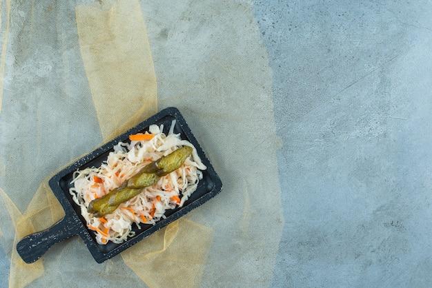 Gefermenteerde zuurkool met komkommer op een bord op een tule, op de blauwe tafel.