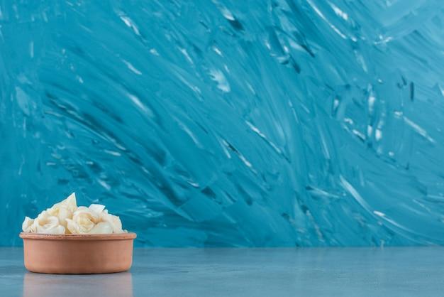 Gefermenteerde zuurkool met wortelen in een kom, op de blauwe tafel.