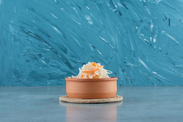 Gefermenteerde zuurkool met wortelen in een kom op een onderzetter op het blauwe oppervlak
