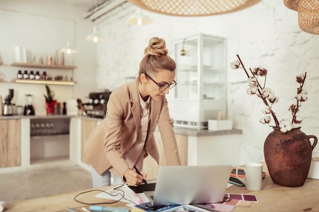 Gefocust blijven. mooie modeontwerper die schetsen maakt die bij de tafel staan met haar laptop.