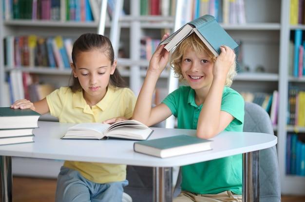 Gefocust hardwerkend donkerharig mooi schoolmeisje en een aardige zorgeloze blonde schooljongen die aan het bureau zit