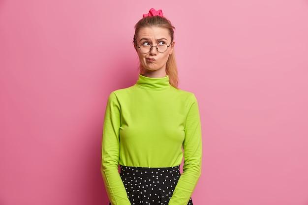 Gefocust schoolmeisje denkt en verzint een idee, tuit de lippen, denkt na over de keuze, heeft een paardenstaart, is goed gekleed, lost een raadsel op, denkt intens