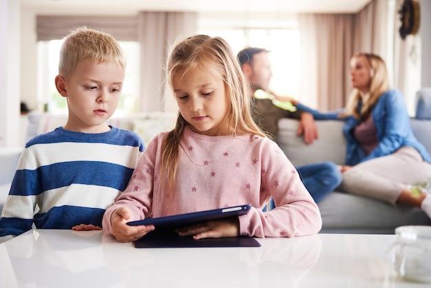 Gefocuste kinderen die technologie gebruiken en ouders