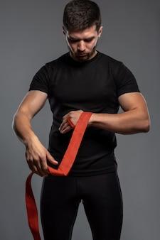Gefocuste man die zijn handen inpakt met bokstape voor het gevecht