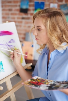 Gefocuste vrouw die aan het schilderij werkt
