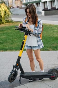 Gefocuste vrouw in het park die voor haar elektrische scooter betaalt met een telefoon-app