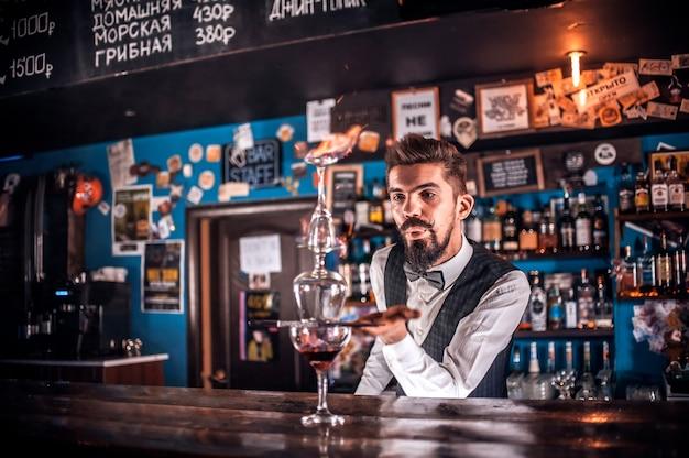 Gefocuste vrouwelijke barman verrast met zijn vaardigheidsbarbezoekers in de nachtclub