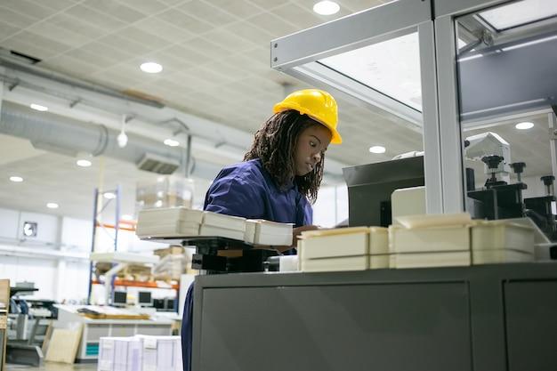 Gefocuste vrouwelijke werknemer van de papierfabriek die veiligheidshelm draagt, industriële machine bestuurt, die zich op de besturingskaart bevindt