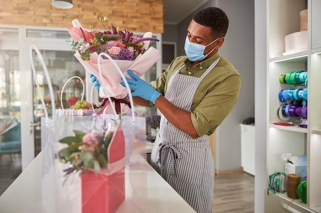 Gefocuste winkelmanager met een gezichtsmasker die een bos bloemen in een lichtpaarse container plaatst