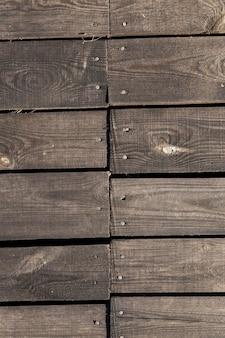 Gefotografeerd close-up deel van de muur gemaakt van planken, zichtbare metalen spijkers voor het bevestigen van bouwmaterialen
