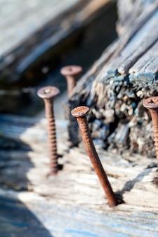 Gefotografeerd dichtbij oude roestige schroef die het bord gebroken banken in het park vastzet