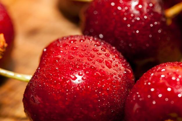 Gefotografeerde close-up van rijpe rode kersen bedekt met waterdruppels, ondiepe scherptediepte