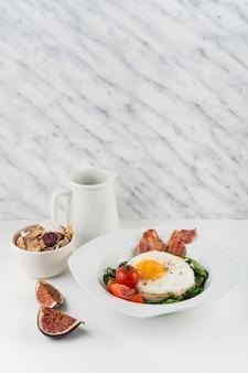 Gefrituurd ei; cornflakes en vijgen op witte achtergrond tegen marmeren gestructureerde achtergrond