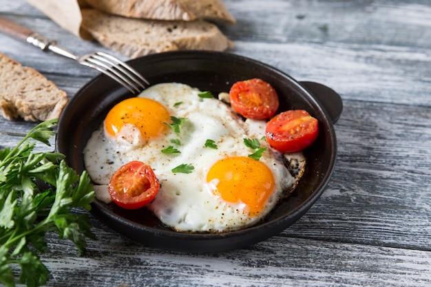 Gefrituurd ei. sluit omhoog mening van het gebraden ei op een pan met kersentomaten en peterselie