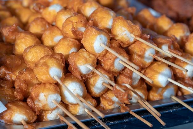 Gefrituurde ballen in diep vet met stokken, thais eten. straat fastfood in thailand, close-up