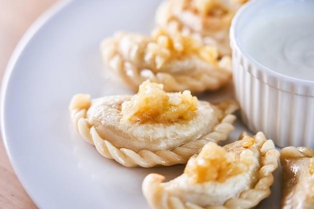 Gefrituurde dumplings gevuld met vlees bestrooid met gekarameliseerde ui op een wit bord white Premium Foto