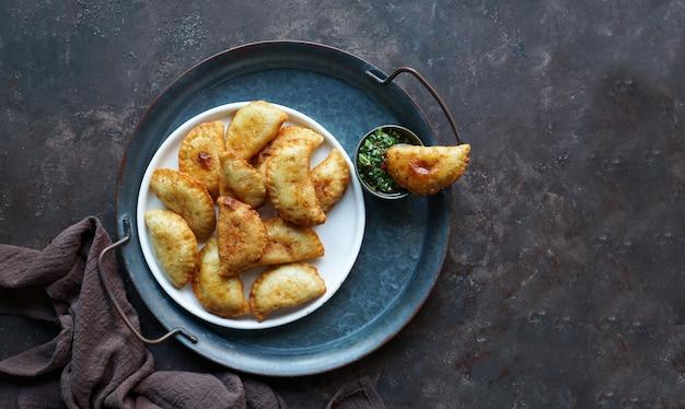 Gefrituurde empanadas met saus. bovenaanzicht