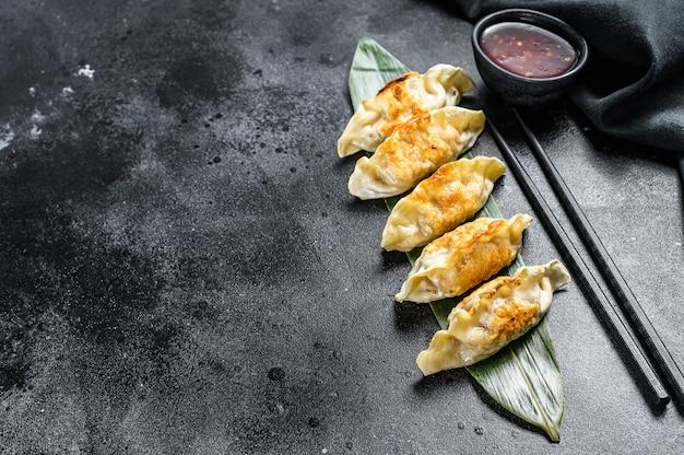 Gefrituurde japanse gyoza-dumplings. zwarte achtergrond. bovenaanzicht. kopieer ruimte.