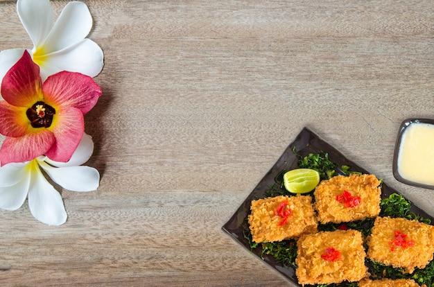 Gefrituurde kip belegd gebakken gesneden rode ui geserveerd met bijgerecht als halve groene citroen. bovenaanzicht op bruin geschilderde houten planken