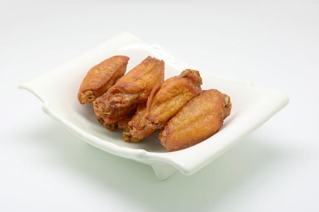 Gefrituurde kippenvleugel met vissensaus op witte plaat en witte achtergrond.
