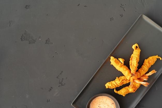 Gefrituurde knapperige garnalen met saus op zwarte ceramische plaat