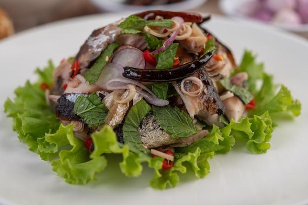 Gefrituurde makreel gegarneerd met laos, peper, munt, rode ui in een witte schotel.