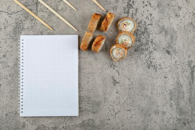Gefrituurde sushi met stokjes en notitieboekje op een stenen achtergrond.