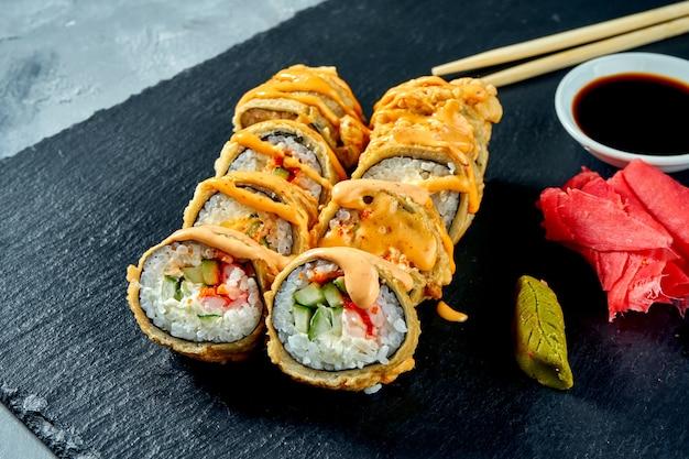 Gefrituurde sushi rolt met garnalen en komkommer in tempura op een zwart leisteen bord. selectieve aandacht selectieve aandacht