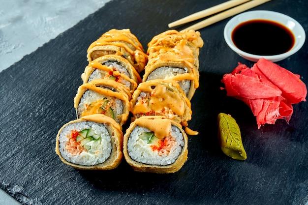 Gefrituurde sushi rolt met zalm en komkommer in tempura op een zwart leisteen bord. selectieve aandacht selectieve aandacht