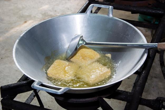 Gefrituurde tofu in een pan met de kokende olie.