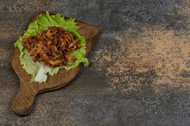 Gefrituurde uien met sla op een houten bord.