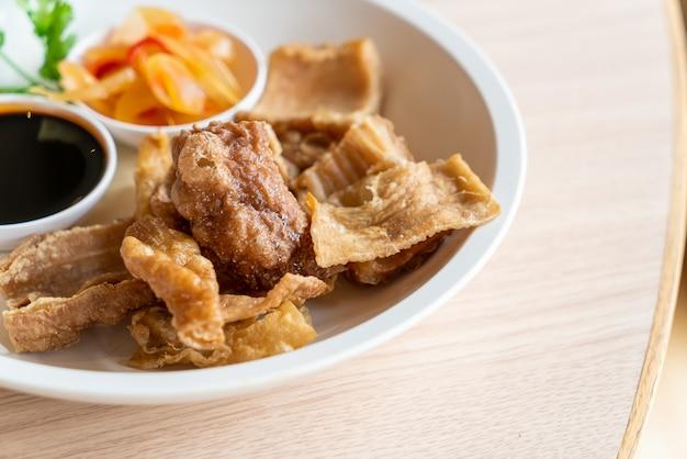 Gefrituurde varkensdarmen met zoete zwarte saus - aziatische eetstijl